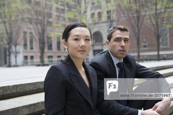 Ein Geschäftsmann und eine Geschäftsfrau sitzen auf einer Treppe