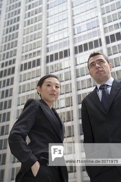 Ein Geschäftsmann und eine Geschäftsfrau vor einem Bürohaus