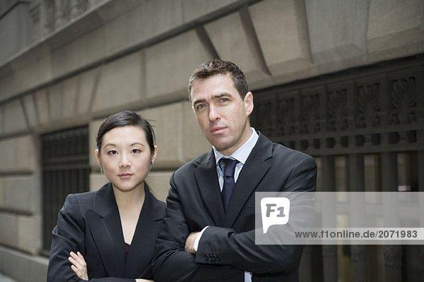 Geschäftsmann und Geschäftsfrau stehen mit verschränkten Armen auf der Straße