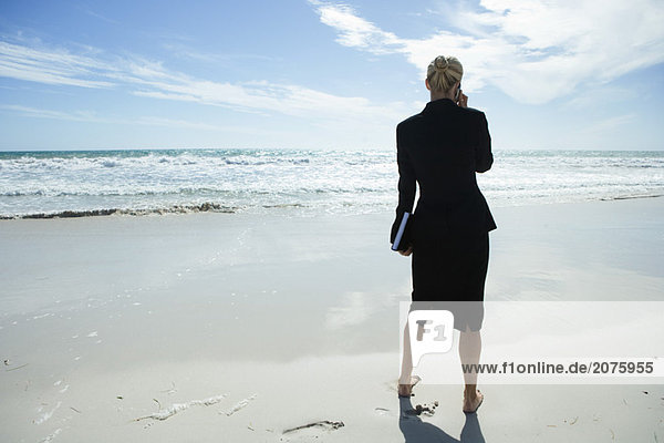 Businesswoman using cell phone  standing on beach barefoot  full length  rear view