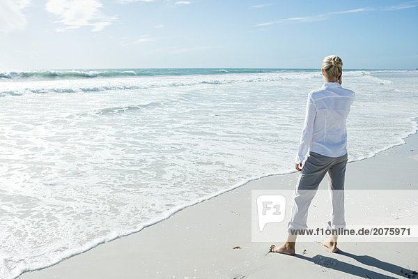 Woman standing barefoot on beach  using cell phone  rear view