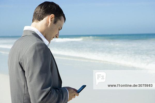 Kaufmann am Strand,  mit Handy