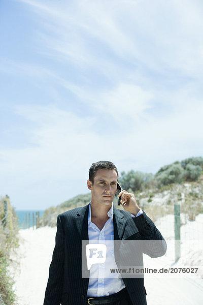 Businessman walking auf Pfad durch Dünen  mit Handy