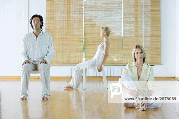 Drei Erwachsene in verschiedenen Haltungen im Wellnesscenter