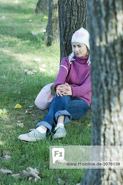 Junge Frau auf Gras  sitzen an Baum gelehnt