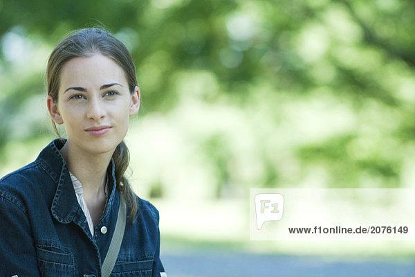 Junge Frau trägt Jacke  Außenaufnahme  Lächeln in die Kamera  Schwerpunkt Vordergrund