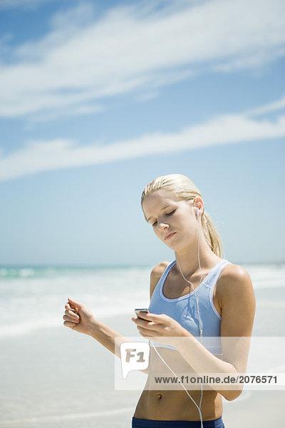 Junge Frau mit MP3-Player am Strand  tragen active wear