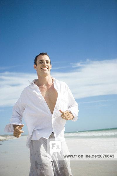 Junger Mann auf Strand  lächelnd