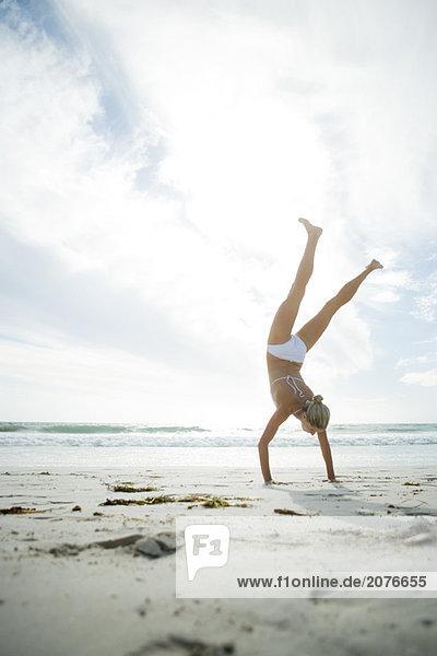 Junge Frau im Bikini stehen auf die Hände auf Strand  in voller Länge