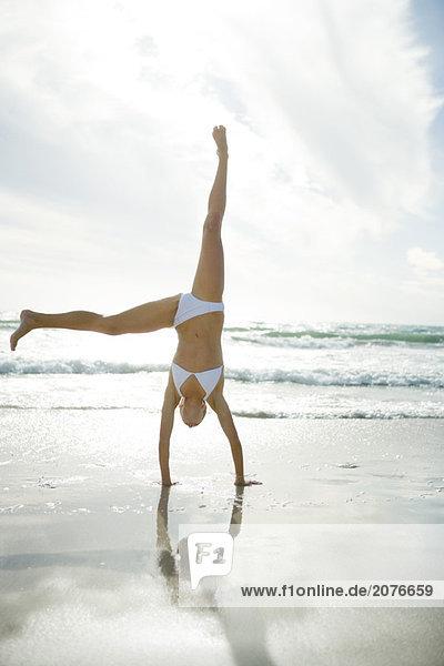 Junge Frau im Bikini Cartwheel am Strand  in voller Länge dabei