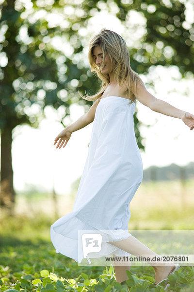 Junge Frau im Kleid zu Fuß in Feld  Waffen aus