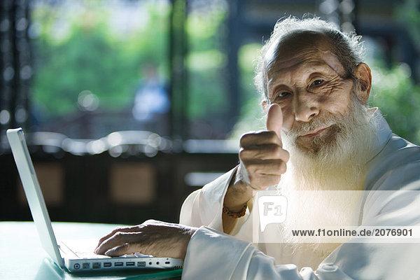 Ältere Menschen Mann tragen traditionellen chinesischen Kleidung  mit Laptop  geben Daumen bis zur Kamera