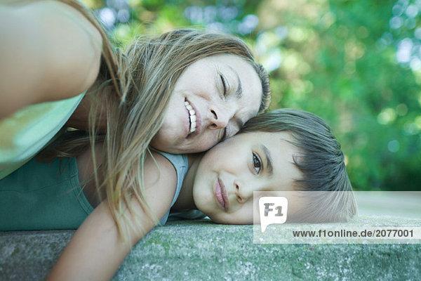 Junge und Mutter liegen  ruht Kopf auf junge  junge Frau lächelnd in die Kamera