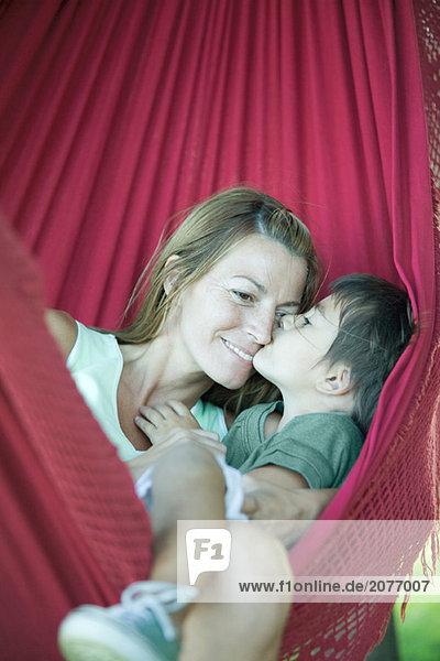Junge und Mutter in Hängematte  küssen woman's Face boy