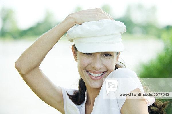 Frau hält hustet auf Kopf  in die Kamera  lächelnd Portrait