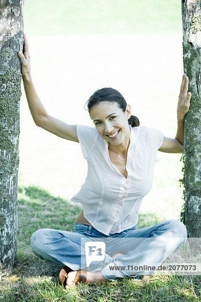 Frau sitzt auf Boden zwischen Holzpfosten  Lächeln in die Kamera