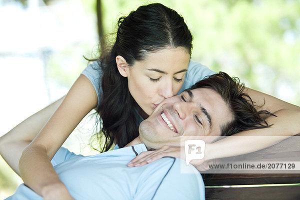 Jungen Paar  Mann sitzend mit Kopf zurück  während Frau Puts kisses Wange