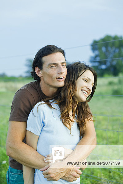 Couple standing in rural setting  laughing  man holding woman from behind