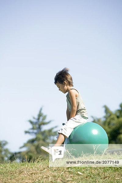 Kleiner Junge im Freien sitzen auf Ball  in voller Länge