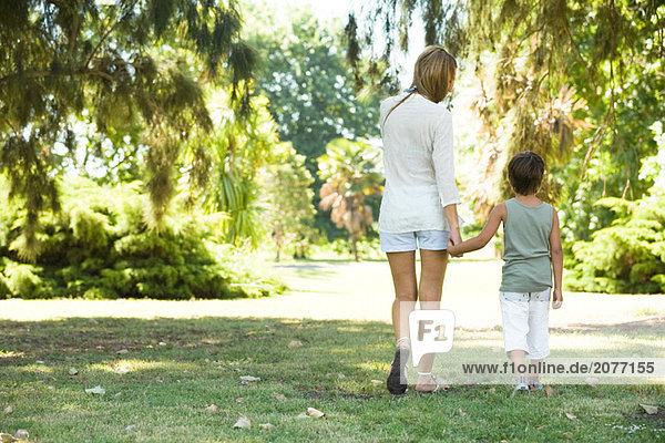 Mutter und Sohn  gehen hand in hand  Rückansicht