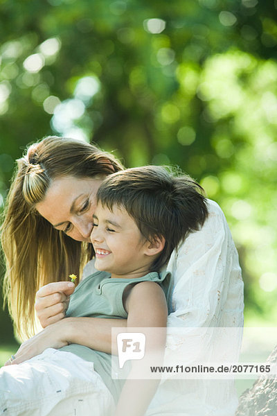 Mutter und Sohn  Junge sitzt auf der Frau Schoß  kichern