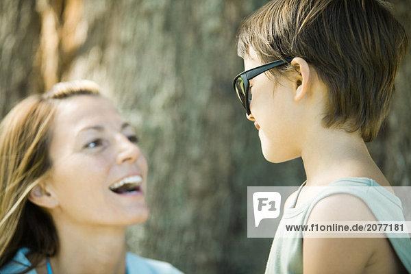 Mutter und Sohn  Boy wearing Sonnenbrille  Frau lachen