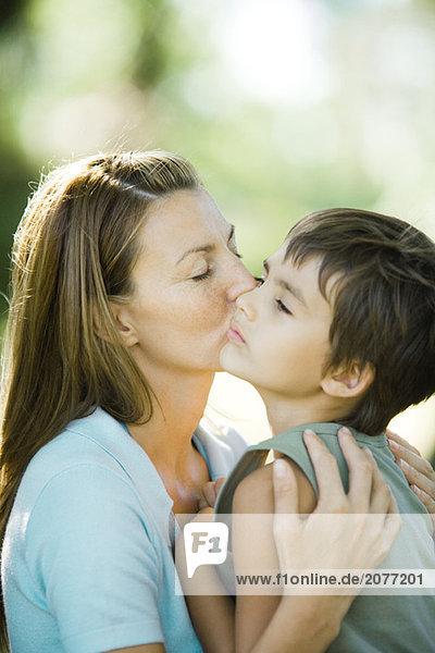 Mutter und Sohn  Frau küssen Boy auf Wange