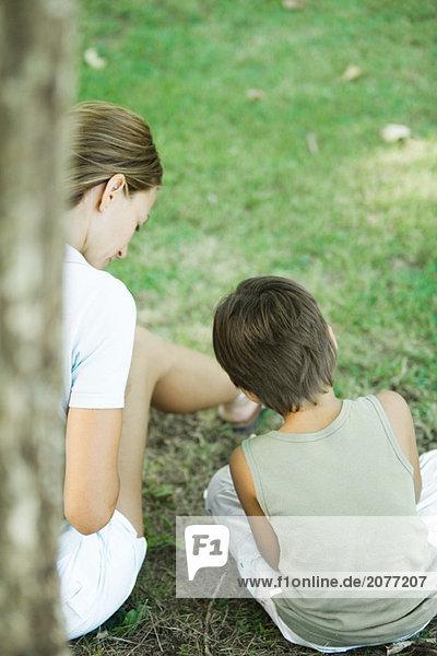 Mutter und Sohn sitzen im Freien  spielen zusammen  Rückansicht