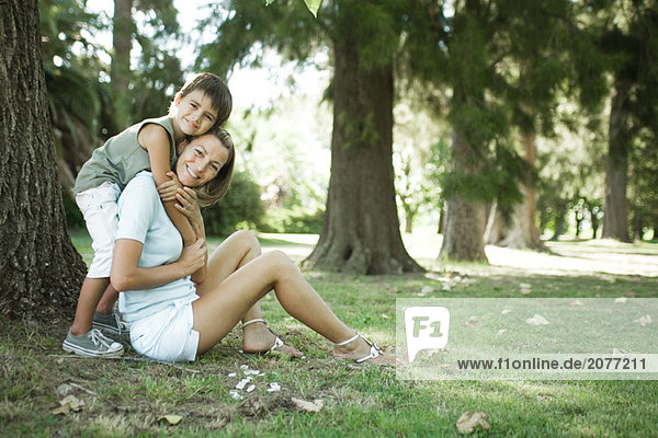 Mutter und Sohn sitzen im Freien  Frau jungbulle knuddeln von hinten