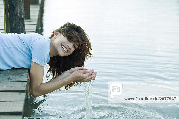 Schiefe Kante des Docks  Frau hält Wasser in hohlen Händen  lachen