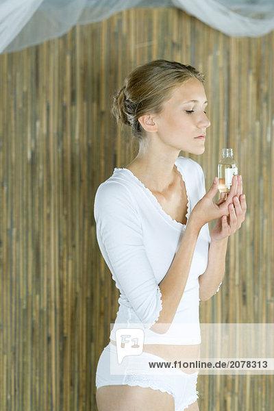 Frau stehend in Unterwäsche  riechen Flasche Körperöl Frau stehend in Unterwäsche, riechen Flasche Körperöl