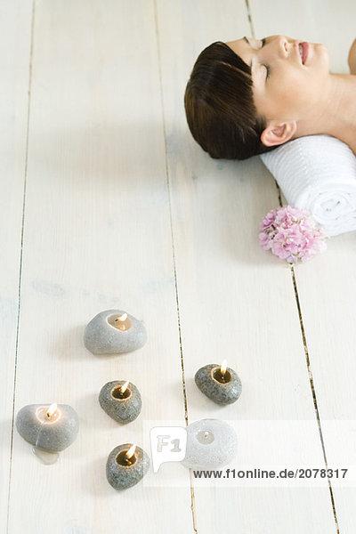 Junge Frau auf Boden  liegen Kerzen an ihrer Seite