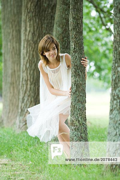 Junge Frau tragen Kleid  um Baum einsehen