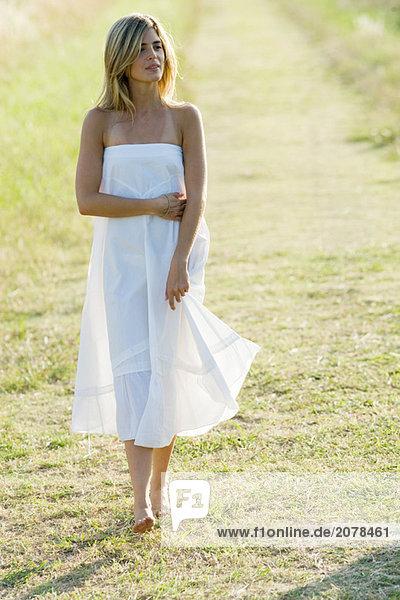 Junge Frau gehen über Gras  in voller Länge