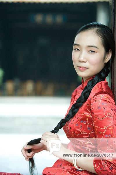 Junge Frau gekleidet in traditionellen chinesischen Clothing  hält ihr lange geflochtene Haar  Blick in die Kamera