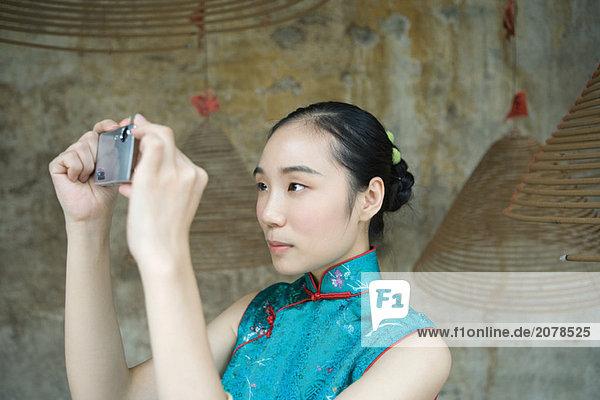 Junge Frau gekleidet in traditioneller chinesischer Kleidung Aufnahme von Fotos mit Digitalkamera