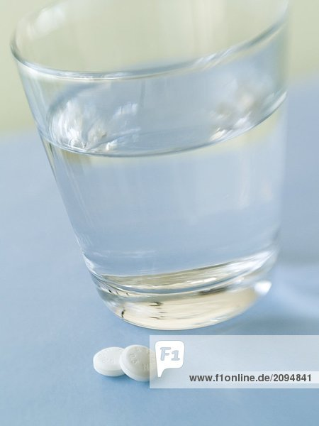 Nahaufnahme-Pillen und Glas Wasser