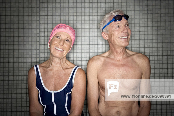 Seniorenpaar im Umkleideraum mit Bademütze und Schutzbrille