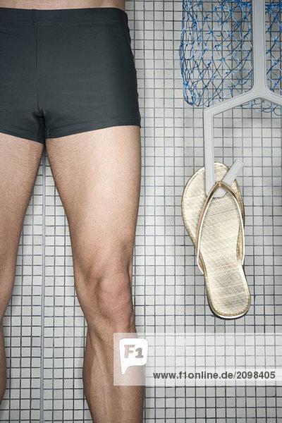 Mann im Umkleideraum stehend  Haltebügel mit Flip-Flops  Unterteil