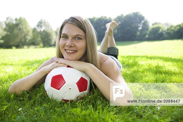 Frau (20-25) im Feld liegend  auf Fußball gestützt  Nahaufnahme