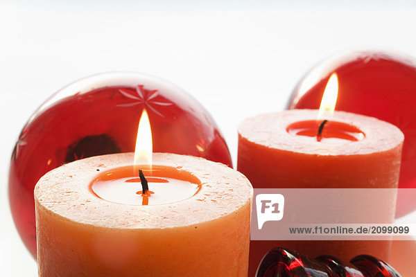 Weihnachtsdekoration mit brennender Kerze und Weihnachtskugeln  Nahaufnahme