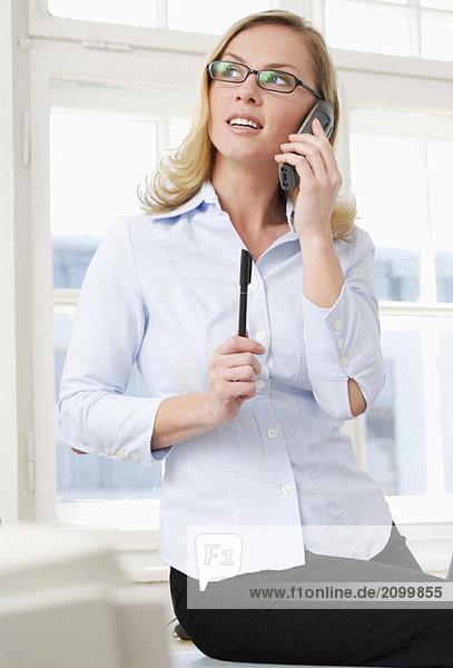 Frau im Büro per Telefon  Nahaufnahme