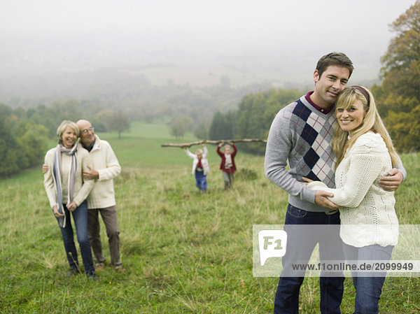 Germany  Baden-Württemberg  Swabian mountains  Two couples embracing  children in background