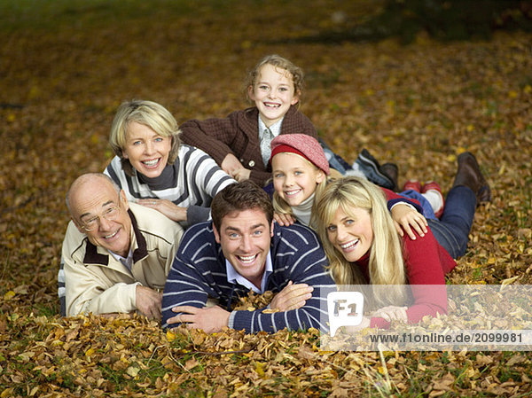 Germany  Baden-Württemberg  Swabiaportrn mountains  Family lying on autumn leaves