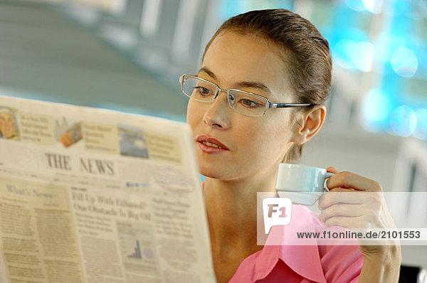 Geschäftsfrau hält Becher und liest Zeitung
