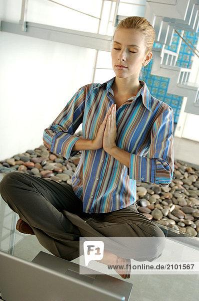 Junge Geschäftsfrau beim Meditieren auf dem Glastisch