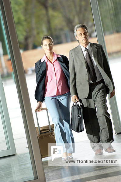 Erwachsener Mann und junge Frau mit Koffer auf dem Flur