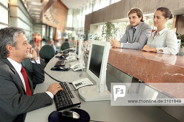 Geschäftsmann am Telefon mit Kollegen am Schalter