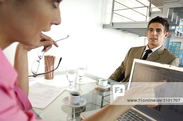 Geschäftsfrau im Gespräch mit Geschäftsmann im Büro