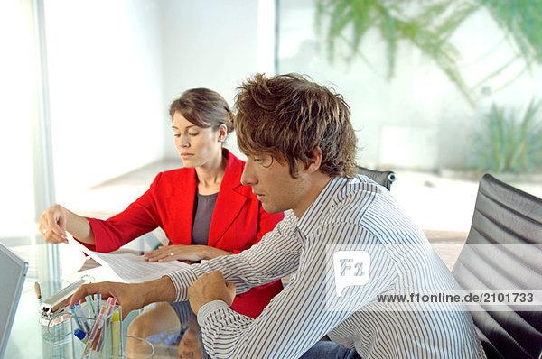 Geschäftsmann und Geschäftsfrau sitzend im Amt